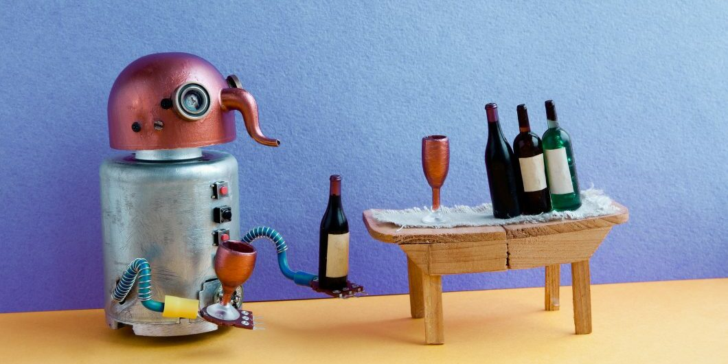 Wine bar party event concept. Funny robot alcoholic drink wine. Creative design copper head cyborg toy gets drunk. Wooden table, bottles, blue yellow room interior